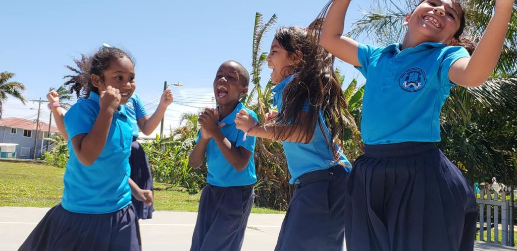 Honduran school children laughing and jumping for the camera