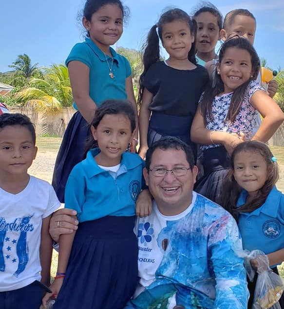 Enrique with a group of children smiling for the camera