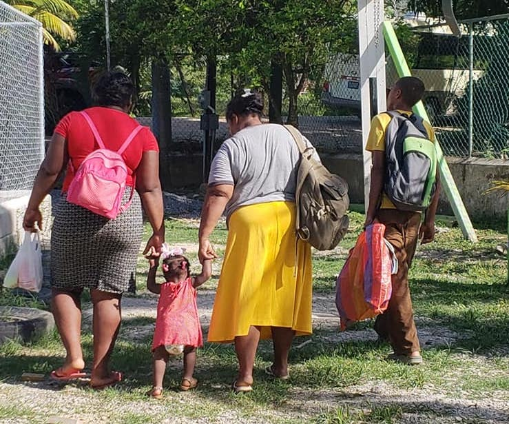 Two women walking, holding the hands of a toddler between them