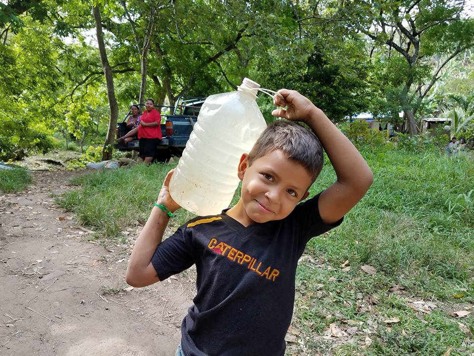 Young boy carry a jug of water on his shoulder