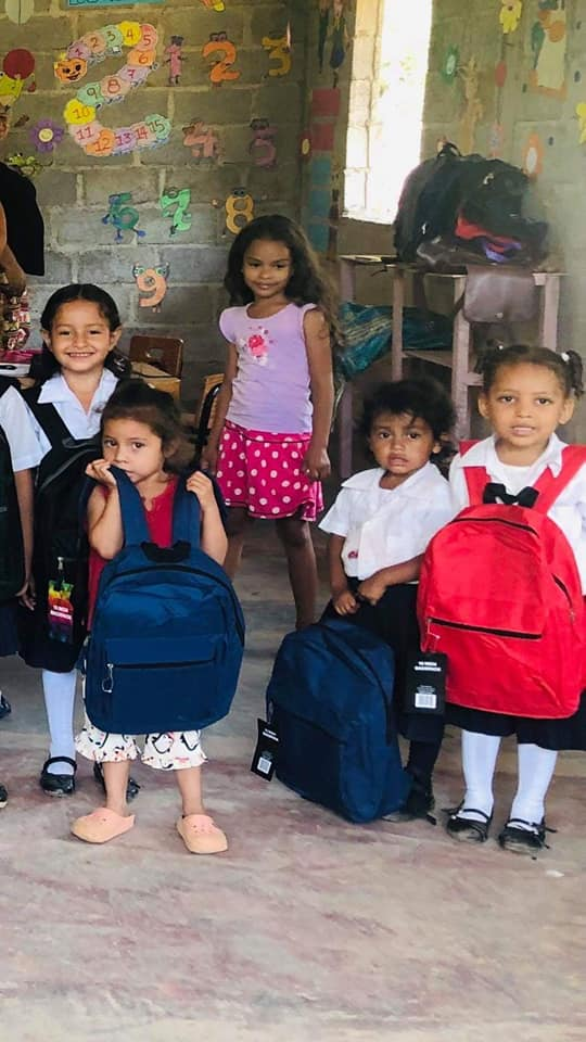 Children in school uniforms pose with their new backpacks