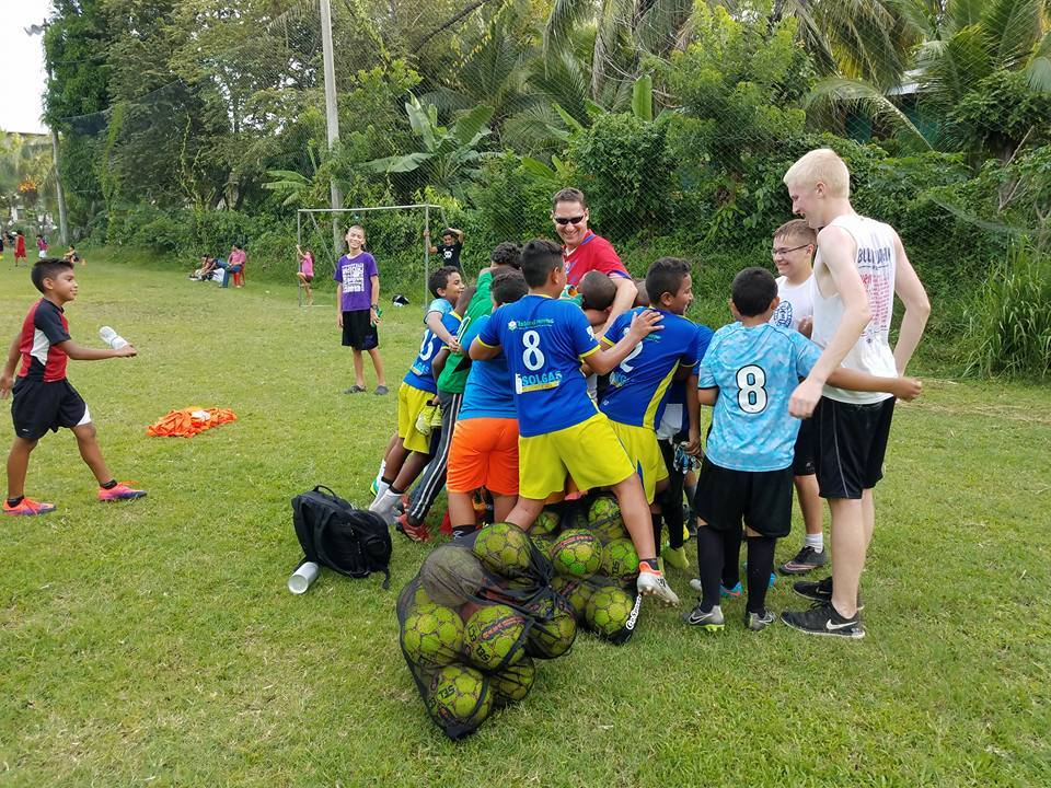 Teenage boy being hugged by a group of young children in soccer uniforms