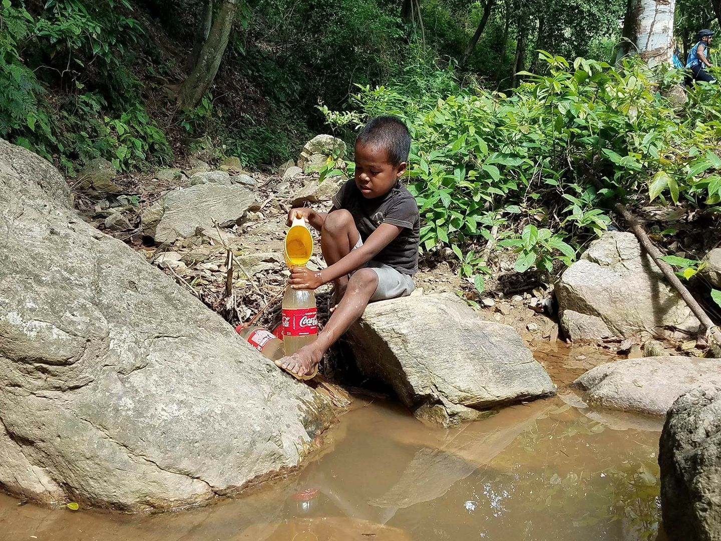Young boy collecting dirty water from a stream into a Coke bottle