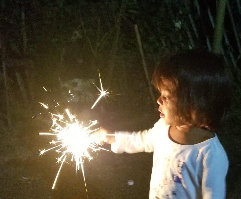 Young girl with a sparkler in the dark