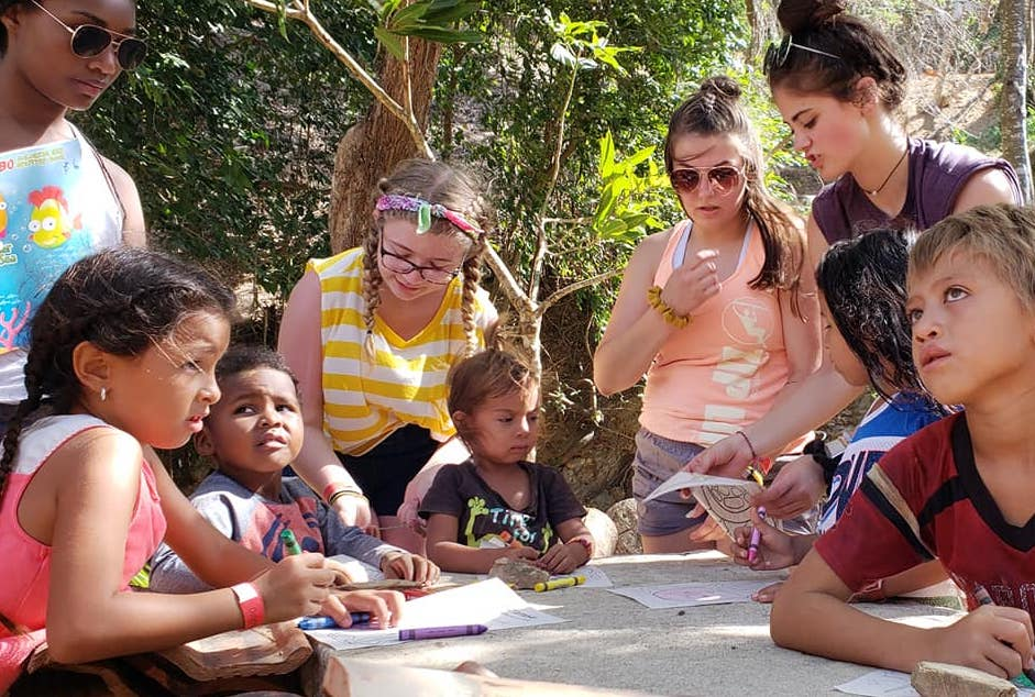 American teenagers coloring with children from Roatan, Honduras