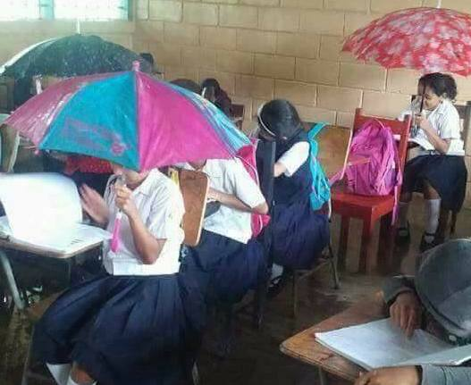 Children using umbrellas in school because the roof is leaking