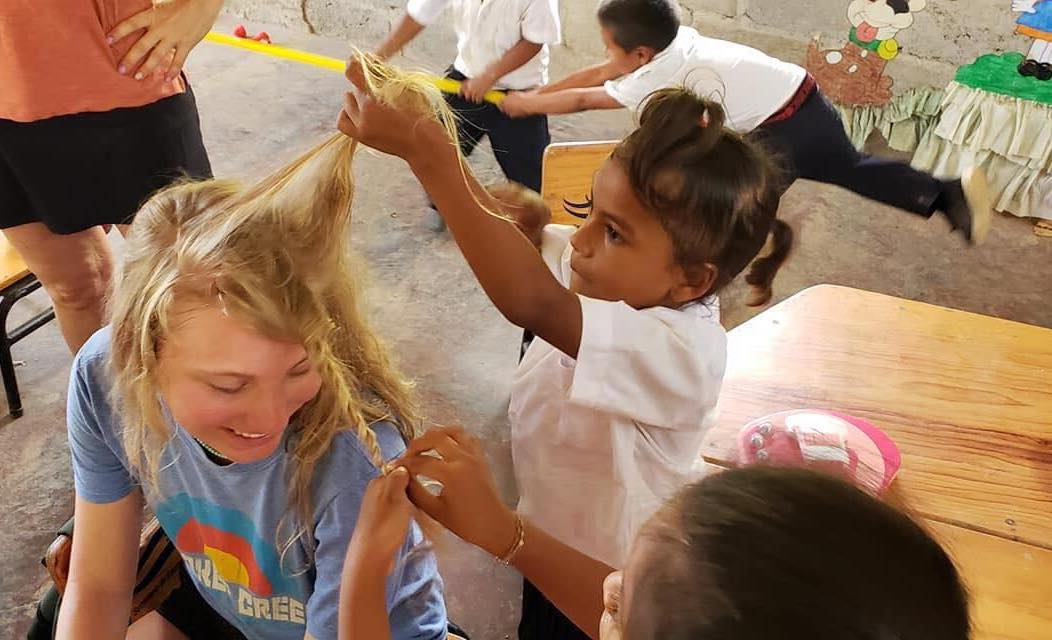 Children playing with a teenage girl's hair
